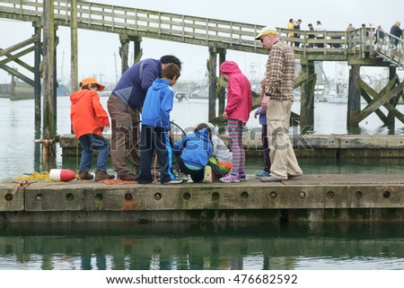 Westport, WA, USA August 21, 2016: Group of children look at crabs in pot while two adults watch over them.