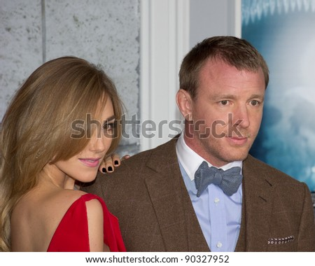 "WESTWOOD, CA - DECEMBER 6: Director Guy Ritchie and Jacqui Ainsley arrive at the premiere of ""Sherlock Holmes: A Game of Shadows"" at Regency Village Theater on December 6, 2011 in Westwood, California - stock photo"