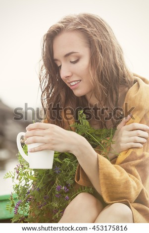 Wet and freezing woman in plaid enjoying a cup of tea with herbs after the rain