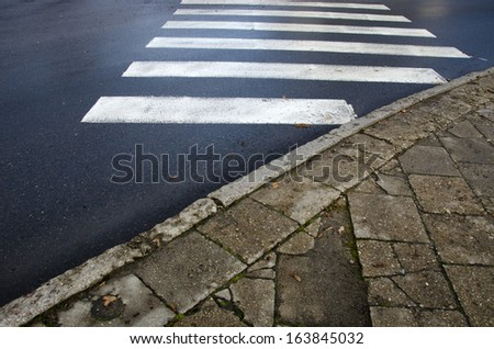 wet asphalt and old concrete pavement bricks. City pedestrian crossing - stock photo