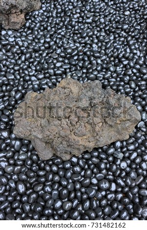 Wet black cobble stone and rock