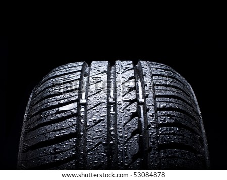 Wet car tire on black background