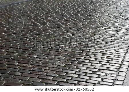 Wet cobblestone road  in sun just after rain. - stock photo