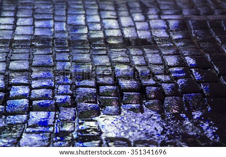 Wet cobblestone road in the winter time. Image taken during night time after the rain. The stones reflects the colors from the colorful advertisement. Image also has a vintage effect applied. - stock photo