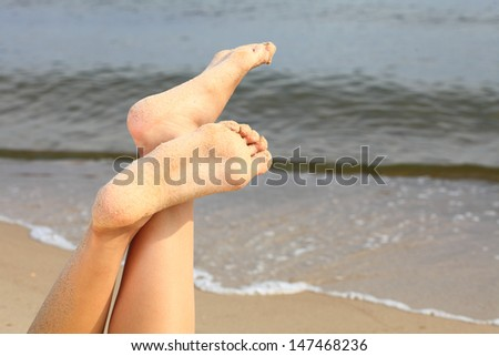 wet female feet on the beach and sand - stock photo