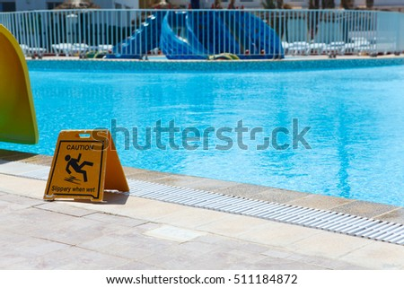Wet floor plate is near swimming pool.