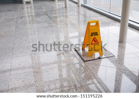 wet floor sign on lobby floor - stock photo
