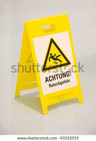 Wet floor warning sign in german - stock photo