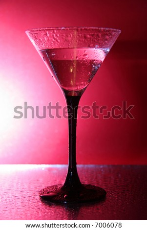 wet glass with martini on the pink background - stock photo