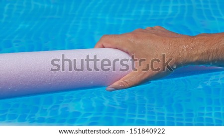 wet hand holding a pool noodle - stock photo