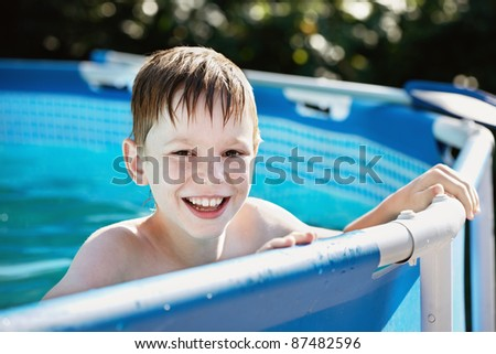Wet, laughing boy looks into the camera out of the pool./Summer pool. - stock photo