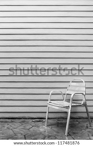 Wet lonely metal chair outside the house after raining - stock photo