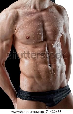 Wet muscular man torso on black white background - stock photo
