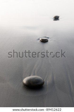 Wet pebbles lie in black sand with bright background, shot vertical - stock photo