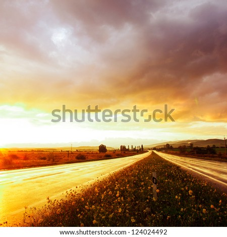 Wet road after rain and sunset over fields - stock photo