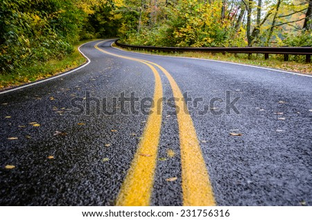 Wet Road in Mountains in Fall - stock photo