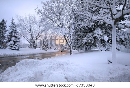 Wet road through snowy winter landscape  in Michigan - stock photo