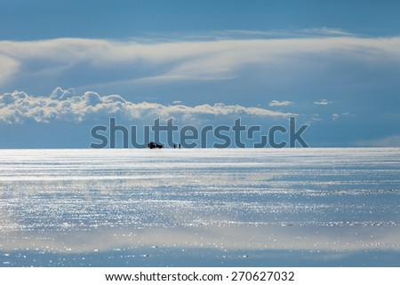 Wet salt surface of the Salares de Uyuni. Reflection of the clouds and sky . 4x4 car with people in the horizon - stock photo