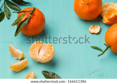 Wet skinless and fresh tangerines on a turquoise kitchen table (horizontal shot) - stock photo