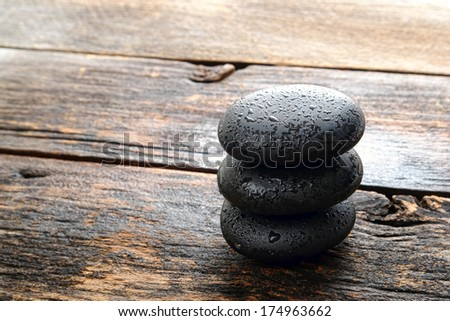 Wet smooth polished black stones with water droplets in Zen style meditation cairn on rain soaked antique weathered wood boards for meditative wellness session and holistic healing rejuvenation   - stock photo