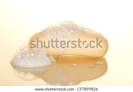 Wet soap with foam on a beige background - stock photo