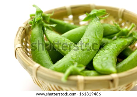Wet sugar snap pea pods in a woven bowl with a white backdrop. - stock photo