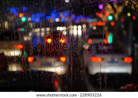Wet the car window with the background of the night city traffic and traffic congestion concept. - stock photo