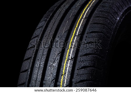 wet tire with asymmetric tread, close-up on a black background - stock photo