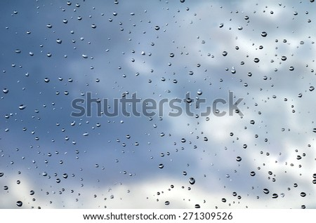 Wet window with rain drops and cloudy stormy sky background - stock photo