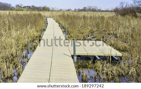 Wetland walkway for nature lovers: Floating boardwalk across prairie marsh in springtime, Moraine Hills State Park in Lake County, Illinois, USA - stock photo