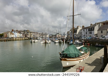 WEYMOUTH, UNITED KINGDOM - AUGUST 26, many boats moored in the canal harbor of touristic historic village of Somerset during summer holidays, shot on  2014 august 26, Weymouth, Dorset, United Kingdom  - stock photo