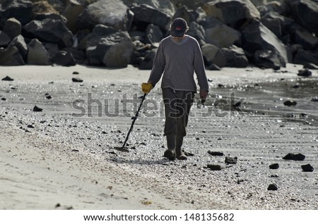 WHANGAREI,NZ - JULY 28:Man using a metal detector on July 28 2013.It's a popular hobby around the world for  treasure hunting, lost jewelry and other valuable items. - stock photo