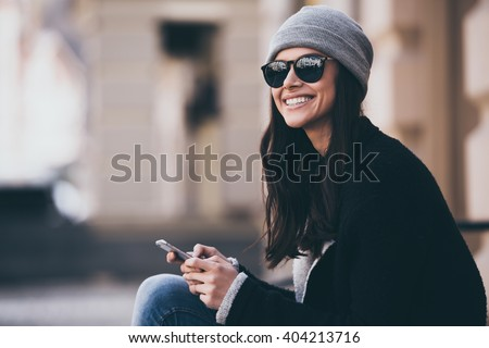 What a beautiful day! Side view of beautiful young woman in sunglasses using her smartphone and looking away with smile while sitting outdoors - stock photo