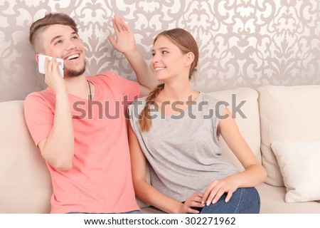 What a great news.  Jubilant smiling young husband sitting on the sofa with his wife and having conversation while holding mobile phone. - stock photo