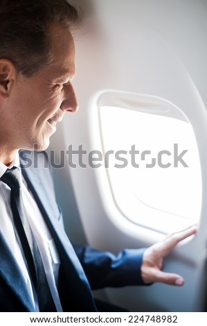 What a great view! Happy mature businessman sitting at his seat in airplane and looking through airplane window - stock photo