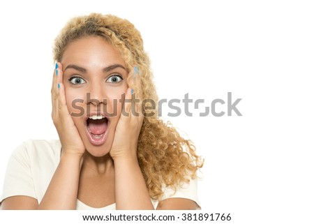 What a surprise. Close up portrait of a young tanned girl with curvy dyed hair standing with her eyes wide opened holding hands near face looking very amazed and shocked, isolated on white background - stock photo