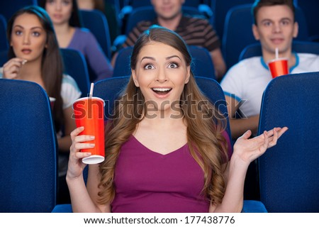What an exciting movie! Beautiful young woman holding cup with soda drink and gesturing while sitting at the cinema  - stock photo