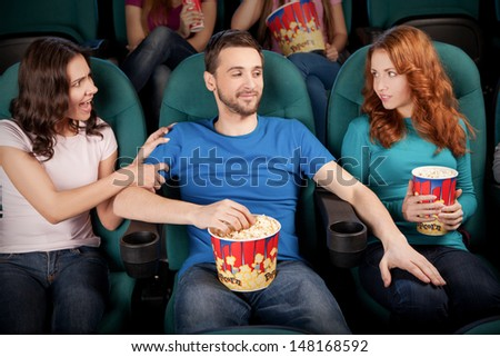 What are you doing? Young men touching the leg of the beautiful stranger women while sitting with his girlfriend at the cinema - stock photo