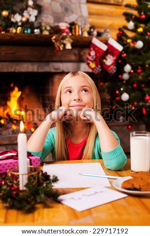What do I wish? Cute little girl day dreaming while sitting at home with Christmas tree and fireplace in the background - stock photo
