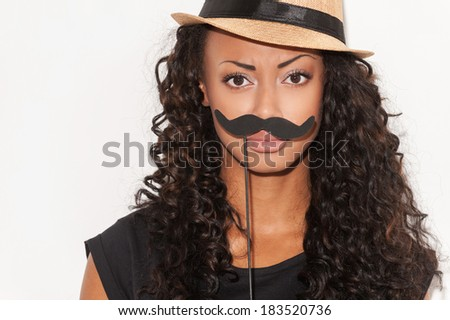 What do you think about my mustache? Portrait of playful young African woman in funky hat holding fake mustache on her face and looking at camera while standing against white background - stock photo