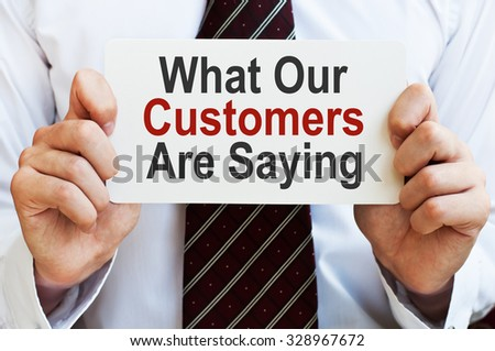 What Our Customers are Saying. Businessman holding a card with a message text written on it - stock photo