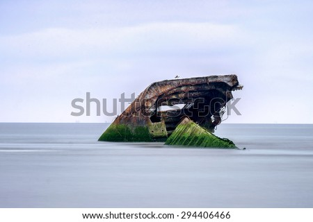 What remains of a sunken Concrete ship on the shore of Cape May Beach - stock photo