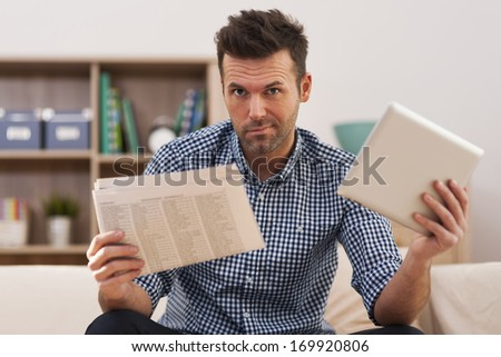 What's better? News from digital tablet or newspaper? - stock photo