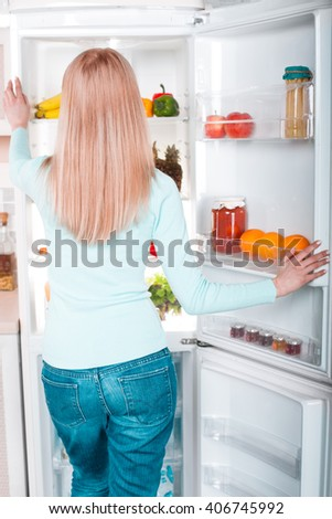 What's for dinner? Pretty blonde standing near open fridge full of food. Back view photo of thoughtful young woman. She looking at fridge - stock photo