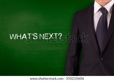 WHAT'S NEXT? on Blackboard with businessman - stock photo