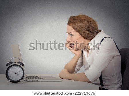 What should I do? Stressed anxious funny looking business woman working sitting in front of laptop pressured by lack of time, panic attack isolated grey office wall background. Human face expression - stock photo
