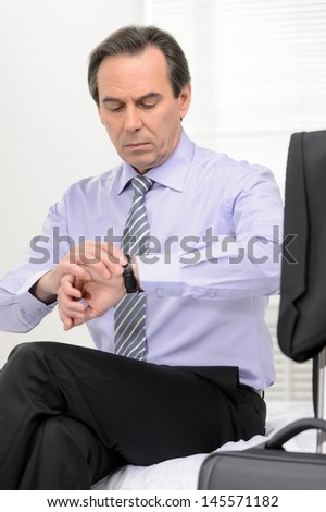 What time is it? Mature businessman looking at his watch while sitting on the sofa with a luggage on the foreground - stock photo