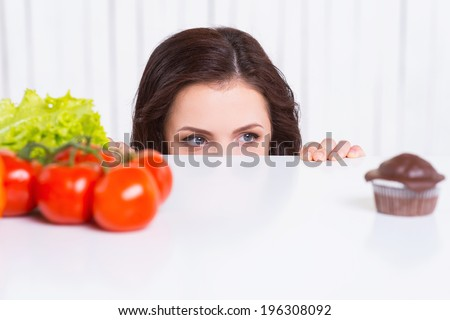 What to choose? Thoughtful young woman looking out of the table while fresh vegetables and chocolate muffin laying on it  - stock photo