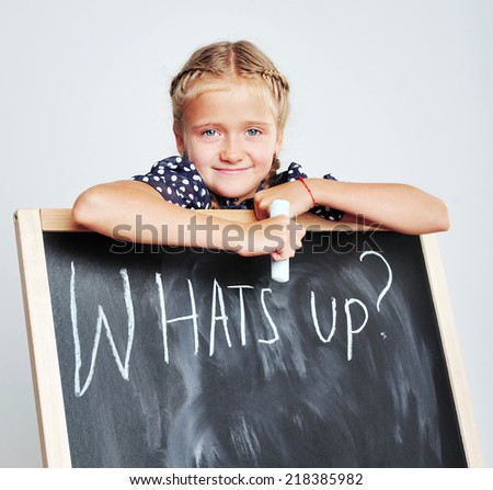 Whats up ? Smiling cute school girl drawing on blackboard - stock photo