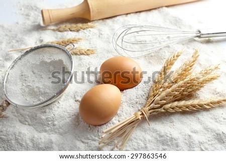 Wheat and eggs on white flour background - stock photo